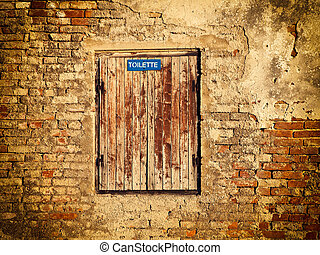 Closed toilette - Old brick wall with an old window and...