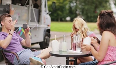 man taking video of friends eating at food truck - leisure,...