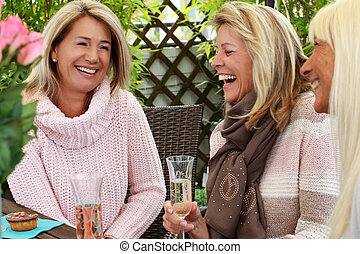 Three mature girlfriends with glasses of sparkling wine -...