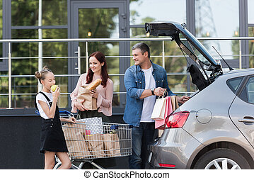 family packing shopping bags in car - beautiful family with...