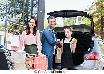 family packing shopping bags in car - beautiful happy family...