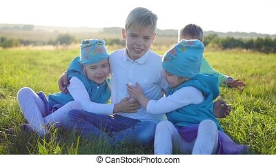 The children sit on the lawn in the Park. Laugh, hug and smile. Children's holiday in the open air