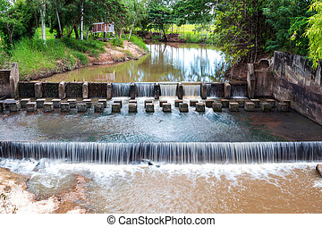 Weir or dam to slow down the flow of water in the river....