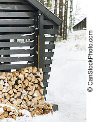 Stack of firewood near the wall of a wooden building