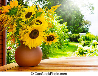 Sunflowers and goldenrod on the garden table