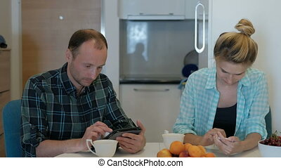 Family drinks tea in kitchen, look at tablet, phone,...
