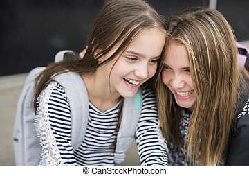 Portrait of two pre teenage girls studying outdoors in...