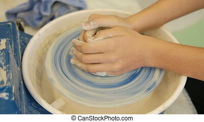 Pupil on the potter's wheel makes dishes under supervision of teacher.