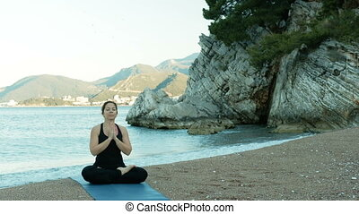 An adult woman meditates with her eyes closed in a lotus...