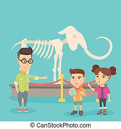 Kids with a teacher studying a skeleton in museum. -...