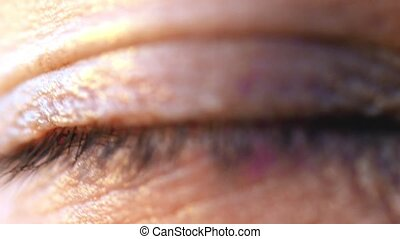 Extreme macro shot of opening of a blue eye of young man in...