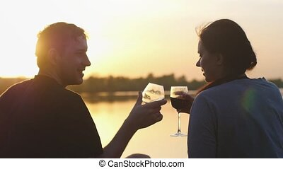 Young couple in love is drinking wine by the sea at sunset. They sit on the sand, clink glasses in slow motion. Anniversary or honeymoon.