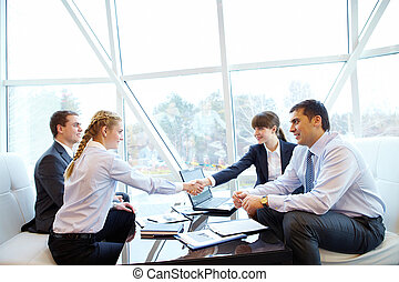 Signing contract - Photo of confident partners handshaking...