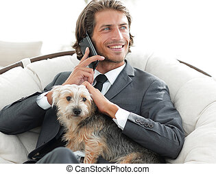 businessman holds his pet and talks on the smartphone while...