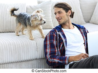 successful guy and his pet in a cozy living room. concept of...