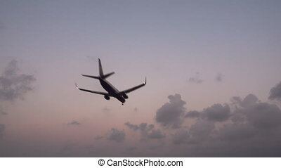 Jet landing at dusk against sky, rear view - Bottom view of...