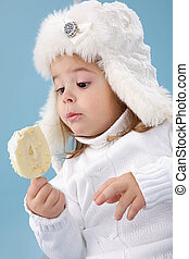 Cutie - Little girl in white furry hat looking at ice-cream...