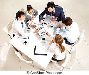 Meeting - Above view of business team sitting around table...