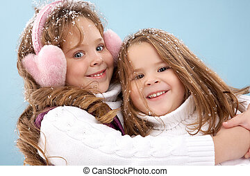 Happy girls - Happy siblings embracing and looking at camera...