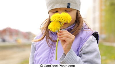 Little girl smelling the yellow flowers