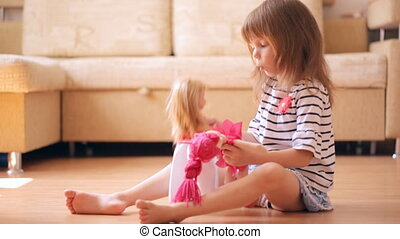 Little girl playing with a dolls