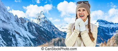 traveller woman in winter outdoors warming hands with breath
