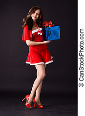 happy smiling woman in red xmas sexy costume with gift