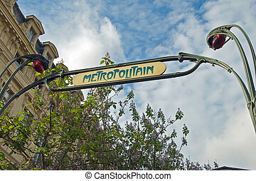 Paris metro entrance sign with a beautiful blue sky in...
