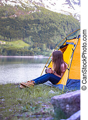 girl hiker sits in a tent - girl hiker in a tent and holding...