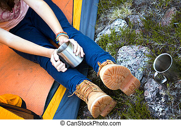 girl hiker holding a cup - girl hiker in a tent and holding...