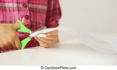 Child's hands cutting paper with scissors
