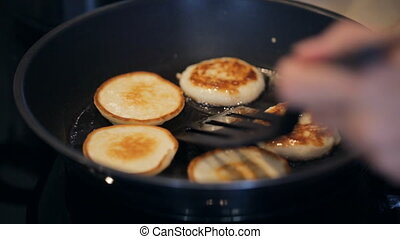 Frying sweet thick pancakes on a pan