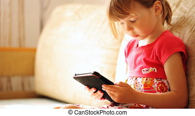 Little girl holding the e-book in her hand's