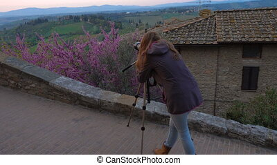 girl taking a picture of tuscanian landscape