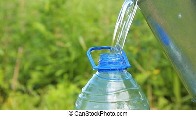 Pouring clean water into the plastic bottle