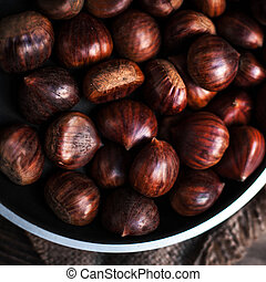 Brown chestnuts in a frying pan on old wooden table close up...