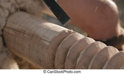 Close-up of the carpenter's hands with the chisel and hammer...