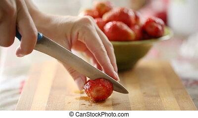 Female hands cutting fresh strawberry