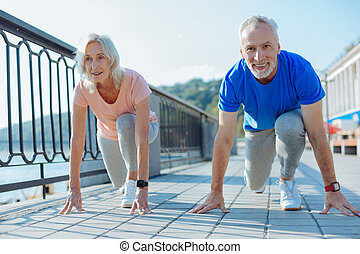Upbeat elderly couple being about to start race - Ready to...