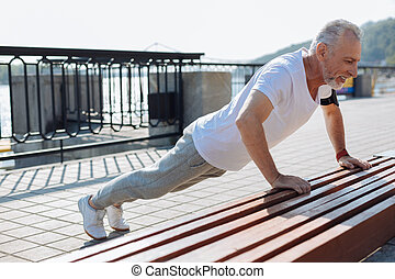 Well-built senior man doing push-ups from bench - Exercising...