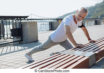 Athletic elderly man stretching near bench - Sports junkie....