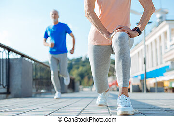 Close up of senior woman doing lunges in the street