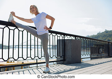 Charming senior woman stretching near bridge balustrade