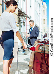 Attractive skillful businesswoman refilling the car - Women...