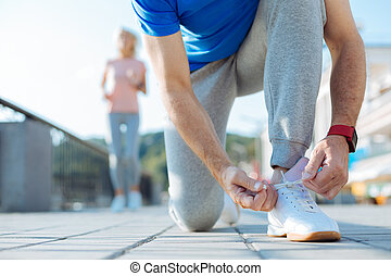 Close up of sporty senior man tying shoelaces on sneaker