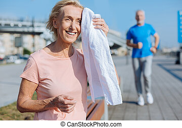 Happy woman wiping sweat from forehead with towel - Sport...