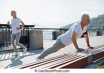 Senior man doing push-ups while his wife jogging - Sporty...