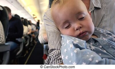 Baby is sleeping in plane with mom in her arms - Close-up of...