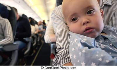 Tired toddler in the plane at the mother's lap. Kid falls...
