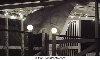 The wind blowing the curtains in an open gazebo at night